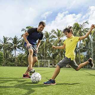 Mann spielt mit Kind Fußball