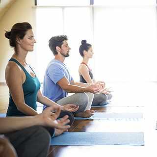 Gruppe bei der Meditation auf Fitnessmatten