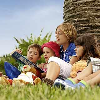 Mehrere Kinder sitzen zusammen und kriegen von der Betreuerin ein Buch vorgelesen