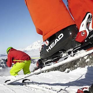 Bunt gekleideter Skifahrer mit Skiern und Skistöcken auf der Piste