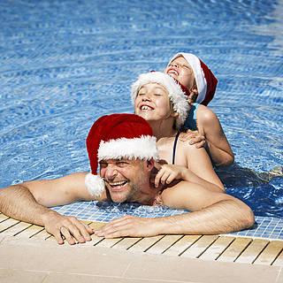 Ein Vater schwimmt mit seinen Kindern im Pool, alle tragen Nikolaus-Mützen