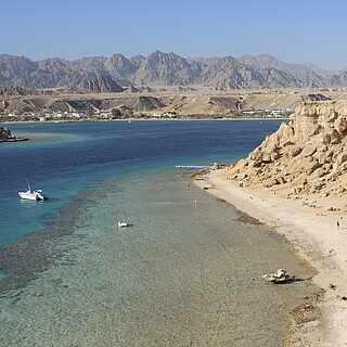 Schroffe Küste mit Blick auf kleine Boote und Wüstenlandschaft