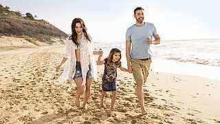 Eltern laufen mit ihrem Kind am Strand entlang und lachen dabei