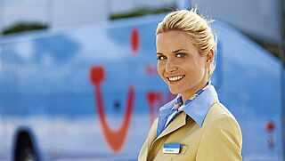 Vor dem TUI Reisebus steht die Reiseleitung in TUI Uniform