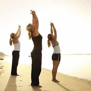Drei Frauen machen Übungen am Strand an der Wasserkante.