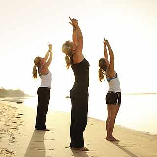 Drei Frauen führen eine Yoga-Figur aus. Sie stehen am Strand nahe des Wassers. Links sieht man Wald.