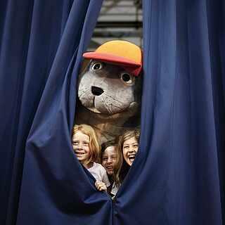ROBINSON Maskottchen lukt mit drei Kindern hinter einem blauen Bühnenvorhang vor