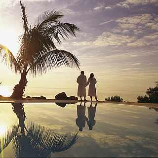 Paar steht im Sonnenuntergang am Pool mit Palmen