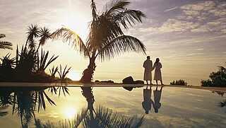 [Translate to Turkish (tr_TR):] Paar steht im Sonnenuntergang am Pool mit Palmen