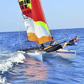 Zwei Männer nehmen and er Catamaran-Week Teil und sind auf einem Katamaran auf dem Meer