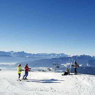 Vier Skifahrer vor einem Gebirge neben einer Seilbahn