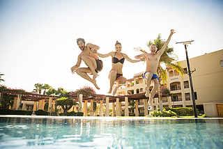 Urlaub mit Freunden, Freunde springen zur Abkühlung in den Pool