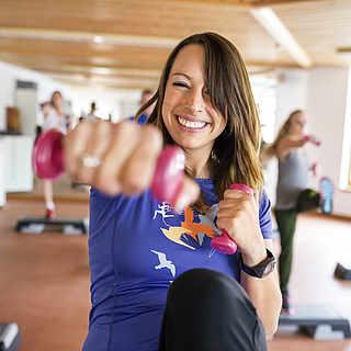 Eine Frau strahlt ihre Motivatoin bei einer Übung aus