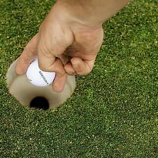 Eine Hand greift Golfball aus einem Golfloch