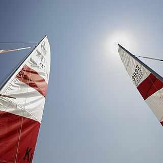 Zwei Katamaran-Segel erstrecken sich in Richtung Himmel, wo die Sonne zu sehen ist.