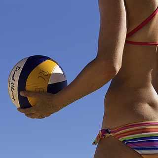 Eine Frau steht mit dem Rücken zu uns und mit einem Beachvolleyball in der Hand