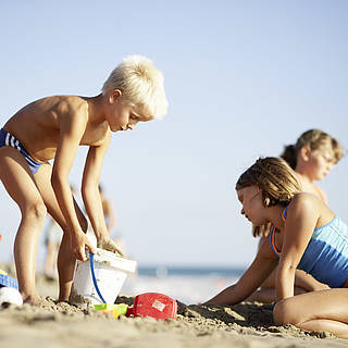 Mehrere Kinder spielen am Strand. Im Hintergrund, ist das Meer zuerkennen
