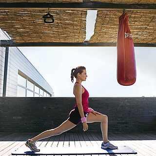 Eine Frau die sich vor einem Boxsack dehnt