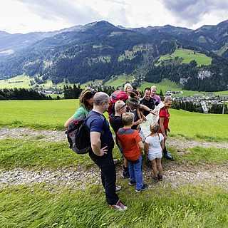 Eine elfköpfige Gruppe steht um eine Wanderkarte herum. Sie befinden sich auf einem unbefestigten Weg. Im Hintergrund ist ein Tal, in dem ein Dorf liegt und dahinter sind bewaldete Berge.
