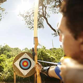 Mann mit Pfeil und Bogen visiert konzentriert eine Zielscheibe