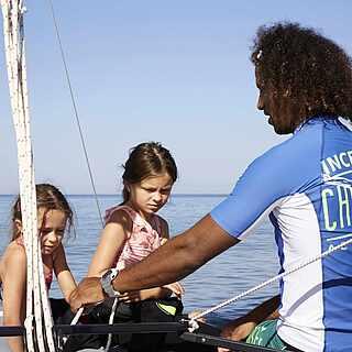 Ein Mann mit zwei Kindern auf einem Boot