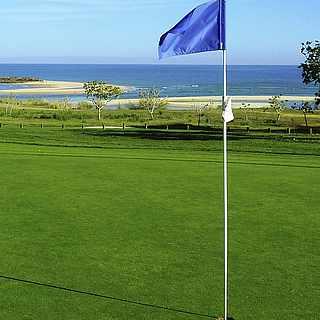 Golfplatz mit Ausblick aufs Meer und blauer Fahne
