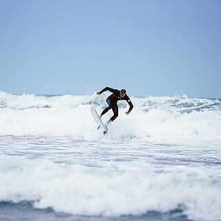 ein Surfer der gerade ein Sprung aus dem Ärmel zaubert