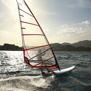 Ein Windsurfer segelt von der Kamera gedreht weg. Hinter ihm sieht man Strand, hügelige Landschaften, hinter dem Segel scheint die Sonne.