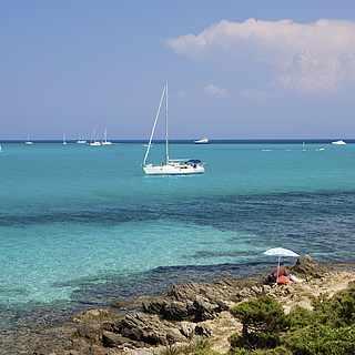 Türkises Meer mit kleinen Booten unter blauem Himmel