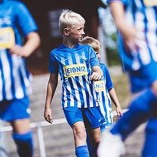 """Kinder in blauen Fußballtrikots mit Aufschrift """"LEIBNIZ"""""""