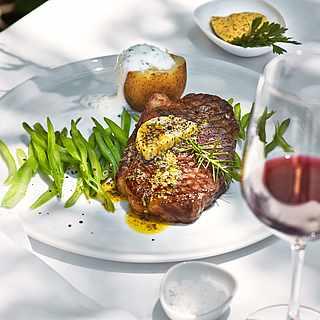 Ein Teller mit einem Filetstück serviert mit Gemüse und einem Glas Rotwein