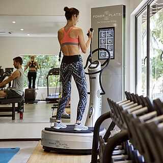 Frau im Fitnessstudio auf Powerplate
