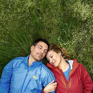 Ein Paar liegt entspannt in einer Wiese mit hohem Gras. Die Frau trägt eine rote Sportjacke, der Mann eine Blaue von Adidas.