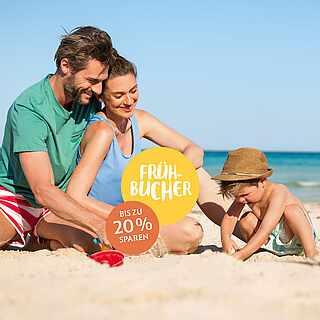 Junge Familie mit Kind am Strand unter blauem Himmel