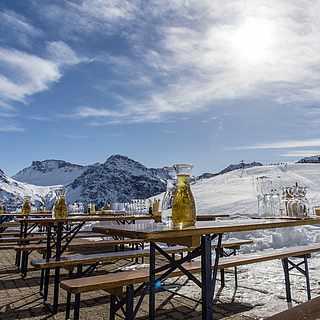 Bänke und Tische stehen draußen vor den Bergen