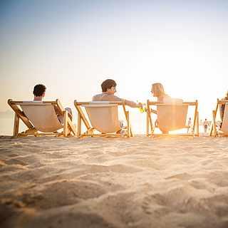 Gruppe junger Pärchen sitzt am Strand auf Liegestühlen und unterhält sich