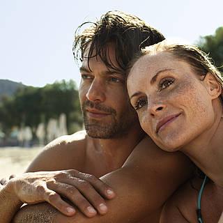 Frau und Mann sitzen frisch gebadet am Strand. Die Frau legt ihren Kopf auf die Schulter ihres Freundes