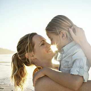 Frau steht am Strand und hält ihr Kind in den Armen