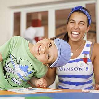 Kind und Betreuerin sitzen am Tisch und lachen in die Kamera