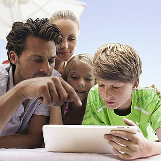 Eine vierköpfige Familie sitzt um das Tablet herum und schaut sich gespannt die ROBINSON App an.