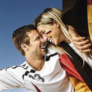 Ein Pärchen das sich umarmt und beim Fußball Deutschland anfeuert