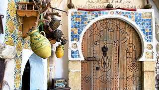 Orientalisch verzierte Holztür mit Rundbogen und bunten Tonkrügen an der Wand